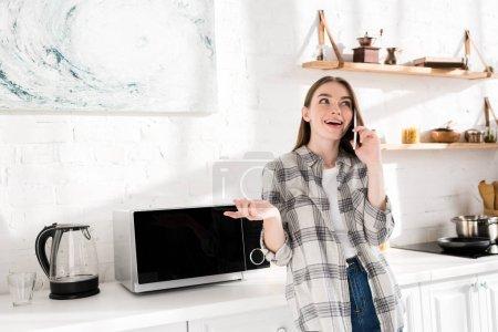 Photo pour Une femme souriante parlant au téléphone intelligent près du micro-ondes dans la cuisine - image libre de droit