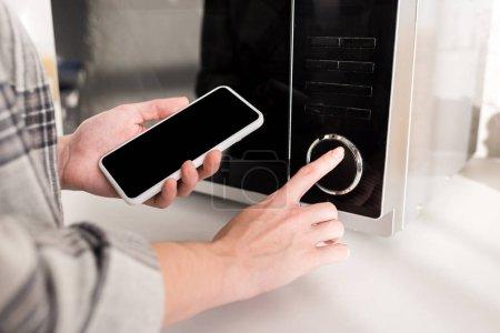 Photo pour Vue recadrée de femme tenant smartphone et utilisant micro-ondes dans la cuisine - image libre de droit