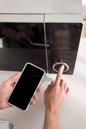 Photo pour Vue en coupe d'une femme tenant un smartphone et utilisant un micro-ondes dans la cuisine - image libre de droit