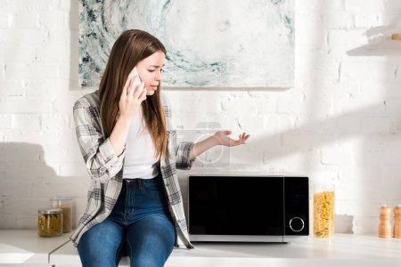 Photo pour Triste femme parlant au téléphone intelligent et regardant le micro-ondes dans la cuisine - image libre de droit