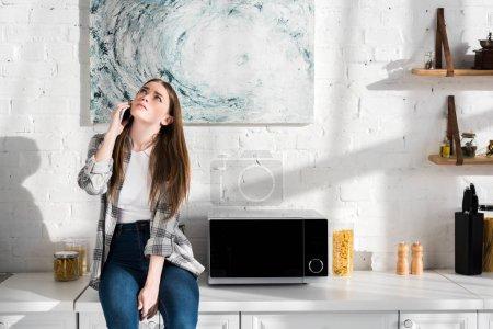 Foto de Mujer triste hablando en teléfono inteligente cerca de microondas en la cocina - Imagen libre de derechos