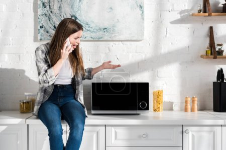 Photo for Angry woman talking on smartphone and looking at microwave in kitchen - Royalty Free Image