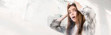 Photo pour Plan panoramique de femme choquée et attrayante regardant loin et touchant la tête - image libre de droit