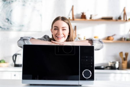 Photo for Smiling and attractive woman standing near microwave in kitchen - Royalty Free Image