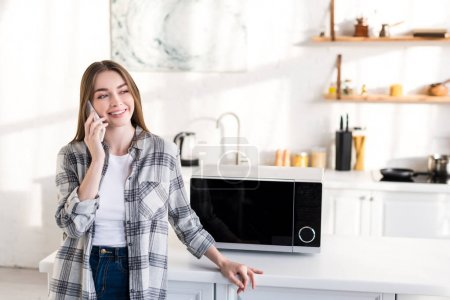 Photo for Smiling woman talking on smartphone near microwave in kitchen - Royalty Free Image