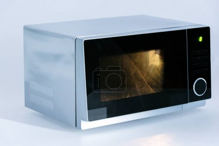 Photo for Metal and electrical microwave oven with light on white background - Royalty Free Image