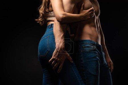 Teilweise Ansicht der attraktiven jungen Frau umarmt sexy Freund isoliert auf schwarz