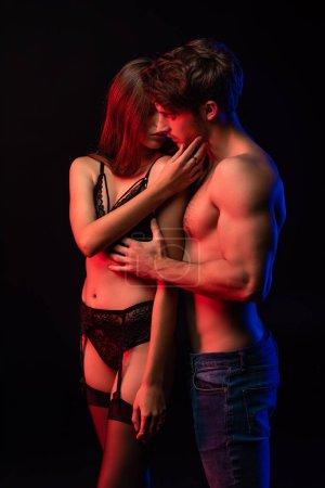 Photo pour Jeune couple nu et sexy s'embrassant à la lumière rouge isolé sur noir - image libre de droit