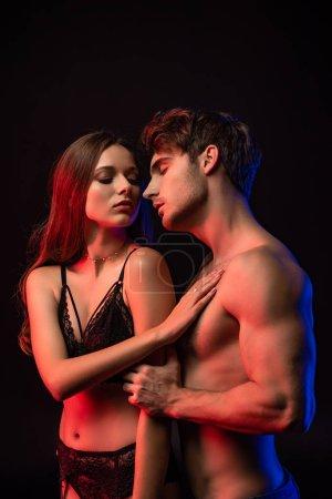 Photo pour Jeune couple sexy sans vêtements se touchant les yeux fermés en lumière rouge isolé sur noir - image libre de droit