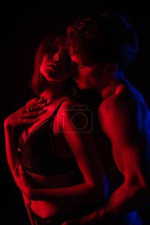 Photo pour Se déshabiller sexy jeune couple embrassant et embrassant dans la lumière rouge isolée sur noir - image libre de droit