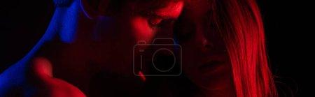 Photo pour Jeune couple nu et sexy s'embrassant en lumière rouge isolé sur une photo panoramique noire - image libre de droit