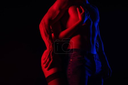 Photo pour Cropping view of passionate undressed sexy young couple touching each other in red light isolated on black - image libre de droit