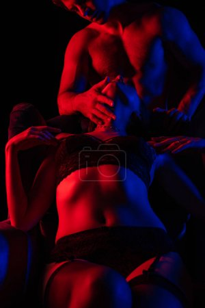 Photo for Man touching sexy woman in underwear in armchair in red light isolated on black - Royalty Free Image