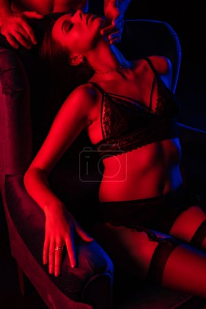 Photo for Partial view of man touching sexy woman in underwear in armchair in red light isolated on black - Royalty Free Image