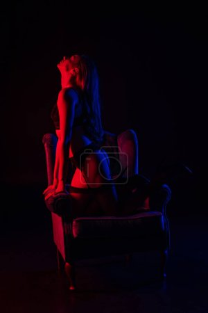 Photo for Sexy woman in lace underwear and stockings on armchair in red light isolated on black - Royalty Free Image