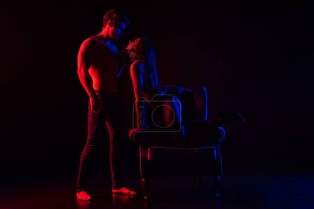 Photo for Sexy woman in underwear in armchair near boyfriend with bare torso in red light isolated on black - Royalty Free Image