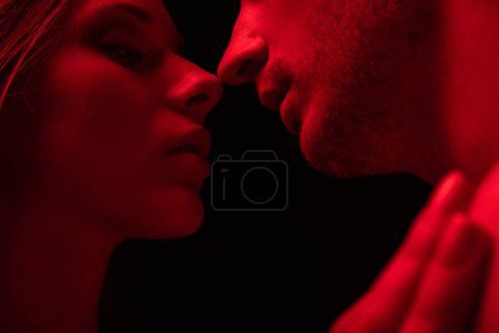 Photo for Passionate sexy young couple kissing in red light isolated on black - Royalty Free Image