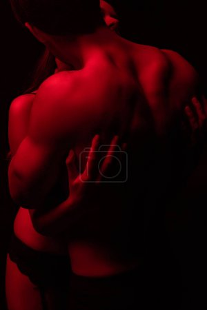 Photo for Passionate undressed sexy young couple hugging in red light isolated on black - Royalty Free Image