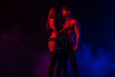 Photo for Passionate undressed sexy young couple hugging in red and blue light on black background - Royalty Free Image