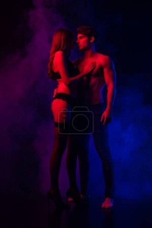 Photo pour Passionnés dévêtu sexy jeune couple serré de lumière rouge et bleue sur fond noir - image libre de droit