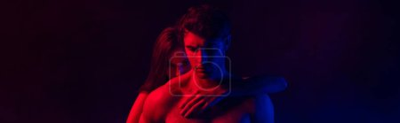 Photo for Naked passionate sexy young couple embracing in red and blue light on black background, panoramic shot - Royalty Free Image