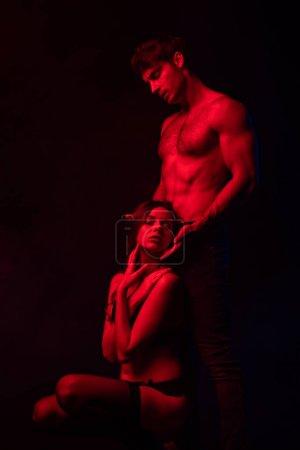 Photo pour Homme sexy dévêtu passionné touchant une femme en lumière rouge isolé sur noir - image libre de droit