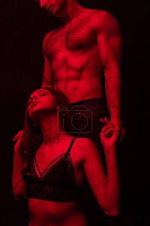 Photo pour Vue partielle d'un homme sexy passionné et déshabillé touchant une femme en lumière rouge isolée sur un noir - image libre de droit