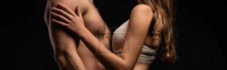 Photo pour Side view of unressed sexy young couple embracing isolated on black, panoramic shot - image libre de droit