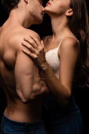 Photo pour Side view of unressed sexy young couple in jeans embracing and kissing isolated on black - image libre de droit