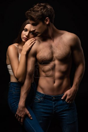 Photo for Undressed sexy young couple in jeans embracing isolated on black - Royalty Free Image