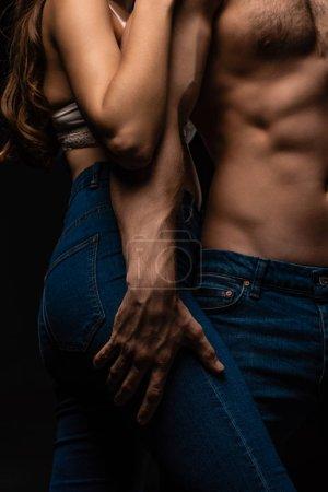 Photo pour Vue recadrée de passionné sexy jeune homme en jeans toucher fille isolé sur noir - image libre de droit