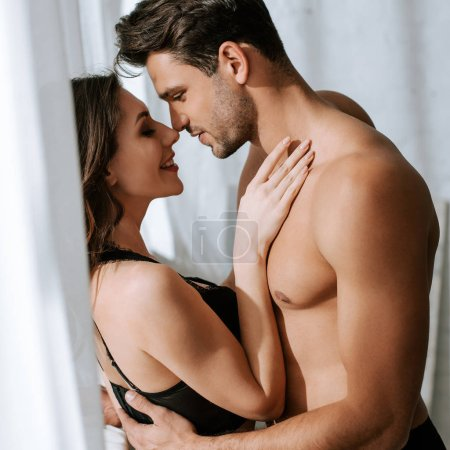 Photo pour Vue latérale de l'homme torse nu étreignant femme heureuse - image libre de droit