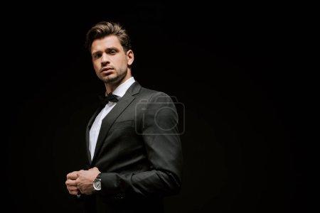 Photo pour Élégant homme en costume regardant caméra isolé sur noir - image libre de droit