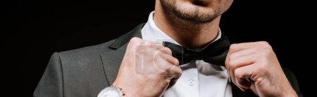 Photo pour Plan panoramique de l'homme touchant noeud papillon isolé sur noir - image libre de droit