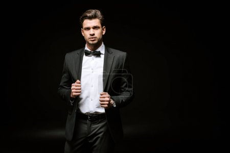 Photo for Elegant man in suit looking at camera and touching blazer on black - Royalty Free Image