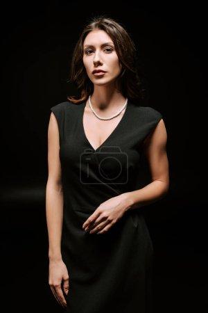 Photo pour Élégante femme en robe regardant la caméra isolée sur noir - image libre de droit
