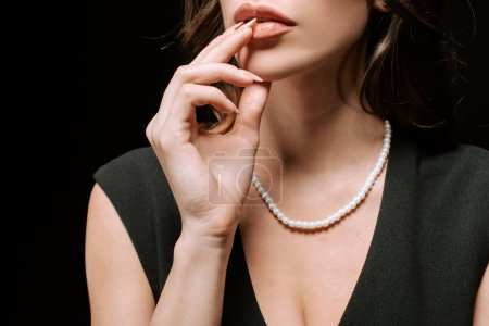 cropped view of woman with pearl necklace on neck touching lips isolated on black