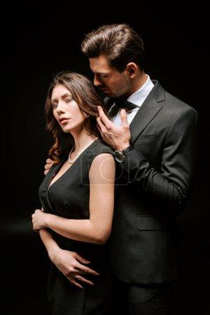 Photo pour Bel homme en costume touchant élégante femme isolée sur noir - image libre de droit