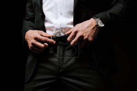 Photo pour Vue recadrée de l'homme touchant la ceinture isolée sur noir - image libre de droit