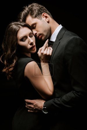 handsome man hugging young attractive woman isolated on black
