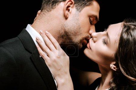 Photo pour Homme baisers avec belle femme isolé sur noir - image libre de droit