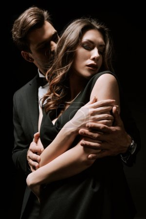 Photo for Man in suit hugging attractive girlfriend in dress isolated on black - Royalty Free Image