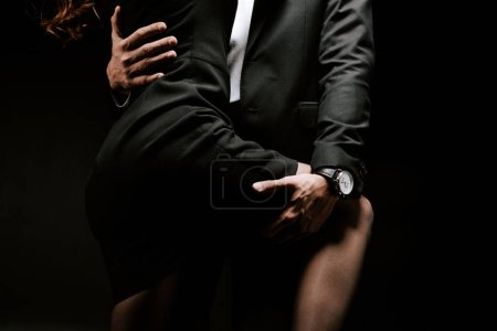 Photo for Cropped view of passionate man holding leg of woman in dress isolated on black - Royalty Free Image