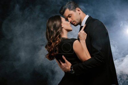 Photo for Attractive woman hugging handsome man on black with smoke - Royalty Free Image