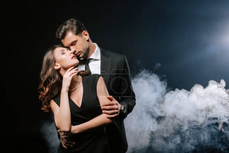 handsome man in suit hugging attractive woman on black with smoke