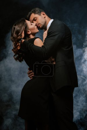 Photo for Handsome man in suit hugging sensual woman on black with smoke - Royalty Free Image