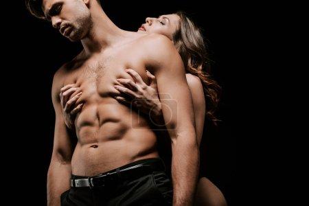 Photo pour Jeune femme passionnée gratter homme sexy isolé sur noir - image libre de droit