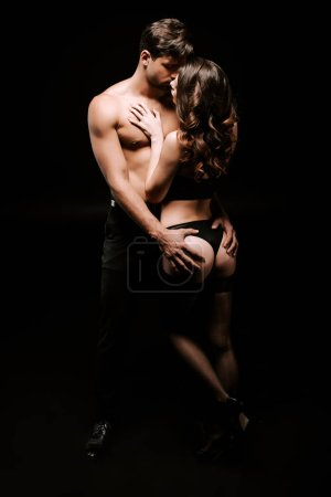 Photo for Shirtless man touching buttocks of sexy girl isolated on black - Royalty Free Image