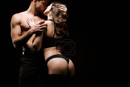 séduisant homme et passionné femme baisers isolé sur noir