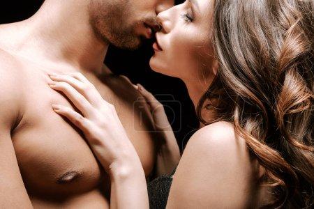 abgeschnittene Ansicht von Mann und Frau, die sich isoliert auf Schwarz küssen